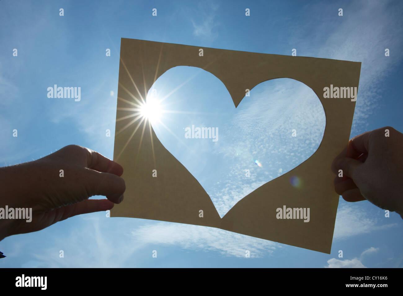 Ein Herz aus Pappe in Den Himmel hat Gegen Die Sonne, ein Herz schneiden Sie ein Stück Papier, zwei Hände Stockbild