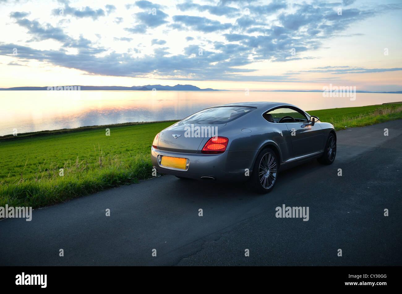 Bentley Continental GT Silber super Auto, Sonnenuntergang Grasgrün Stockbild