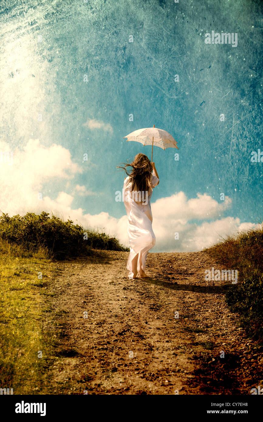 eine Mädchen in einem weißen Kleid ist Fuß in den Dünen mit einem Sonnenschirm Stockfoto