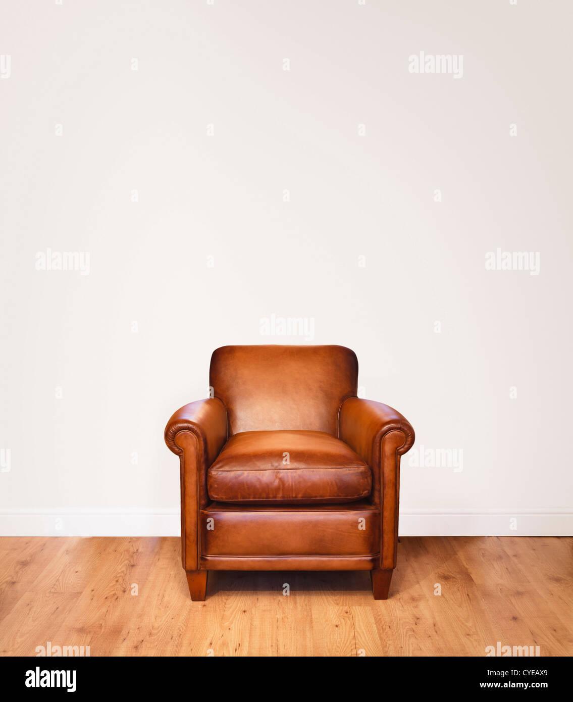Ledersessel auf einem Holzfußboden vor einem weißen Hintergrund mit viel Platz für die Kopie.  Die Stockbild