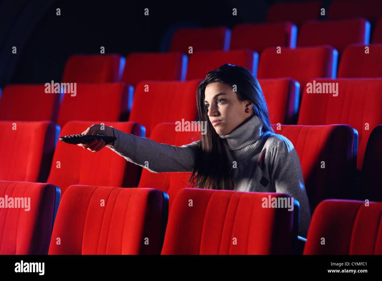 eine junge Frau mit einer TV-Fernbedienung, können Sie im Hintergrund die roten Stühle in einem Kino sehen. Stockbild