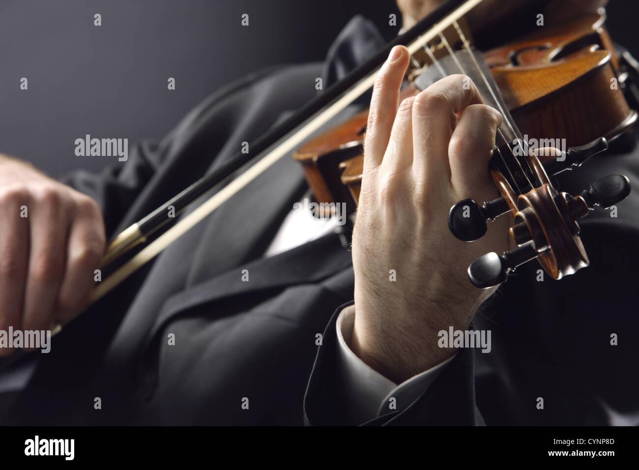 der Geiger: Musiker, spielt Geige auf dunklem Hintergrund Stockbild