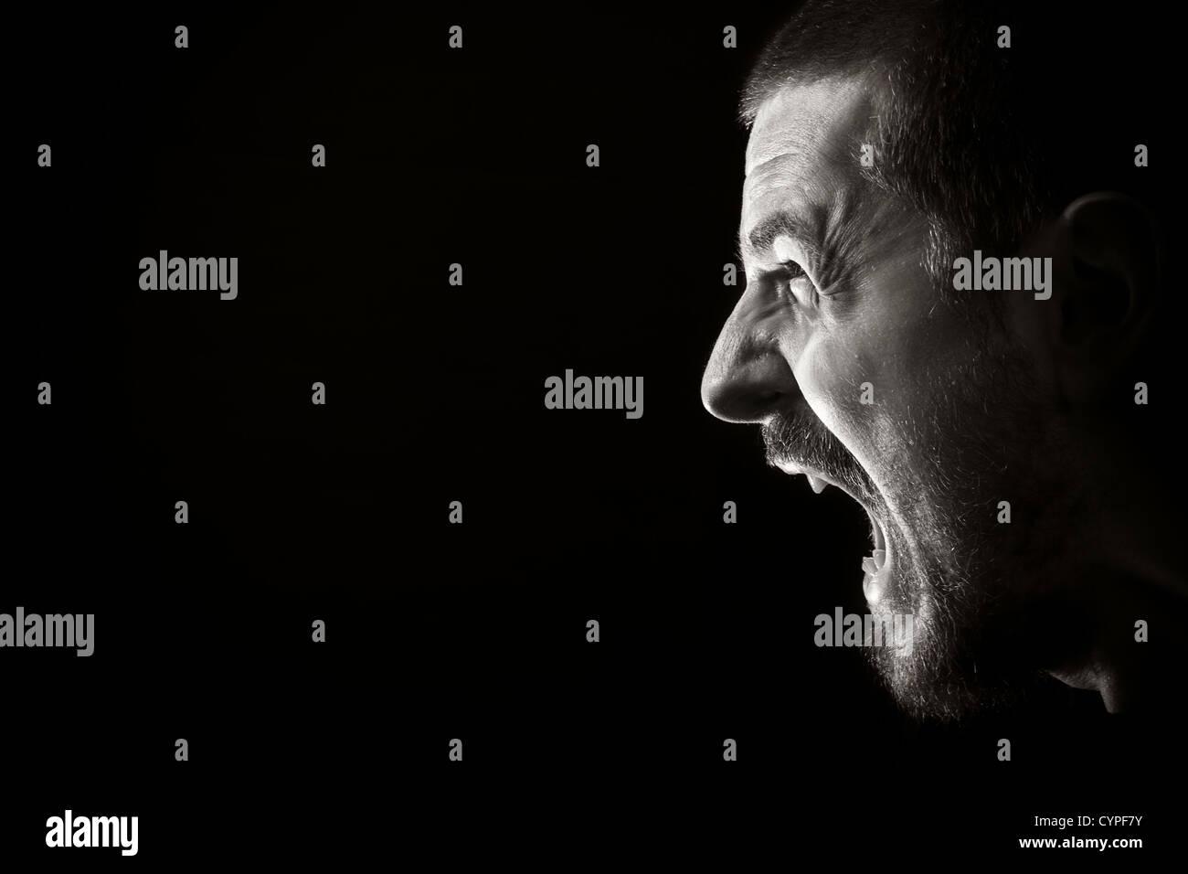 Porträt von kreischenden zorniger Mann auf schwarzem Hintergrund Stockbild