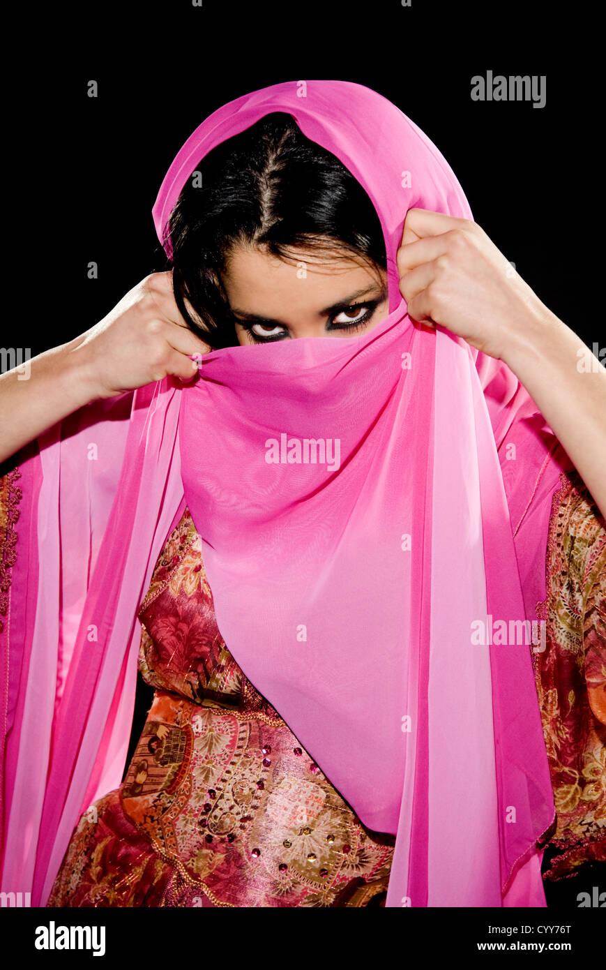 Arabische Frau tragen traditionelle Kleidung auf schwarzem Hintergrund Stockbild