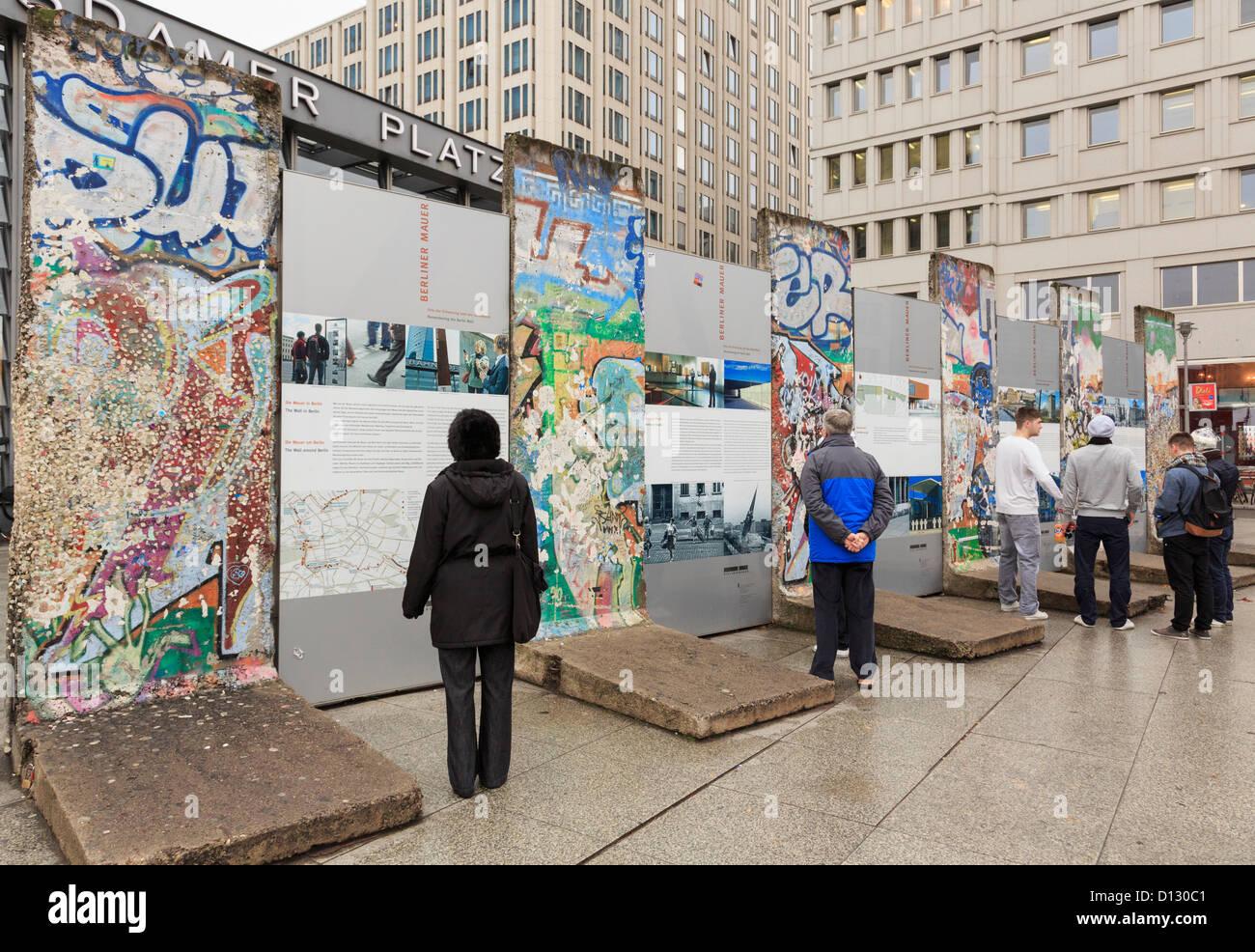Street Scene mit Touristen Lesen von Informationen durch Teile der Mauer jetzt mit Graffiti im ehemaligen Todesstreifen Stockbild