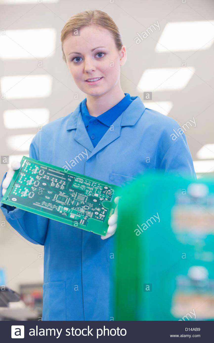 Porträt von lächelnden Ingenieur mit gedrucktes Leiterplatte im Werksgelände Stockbild