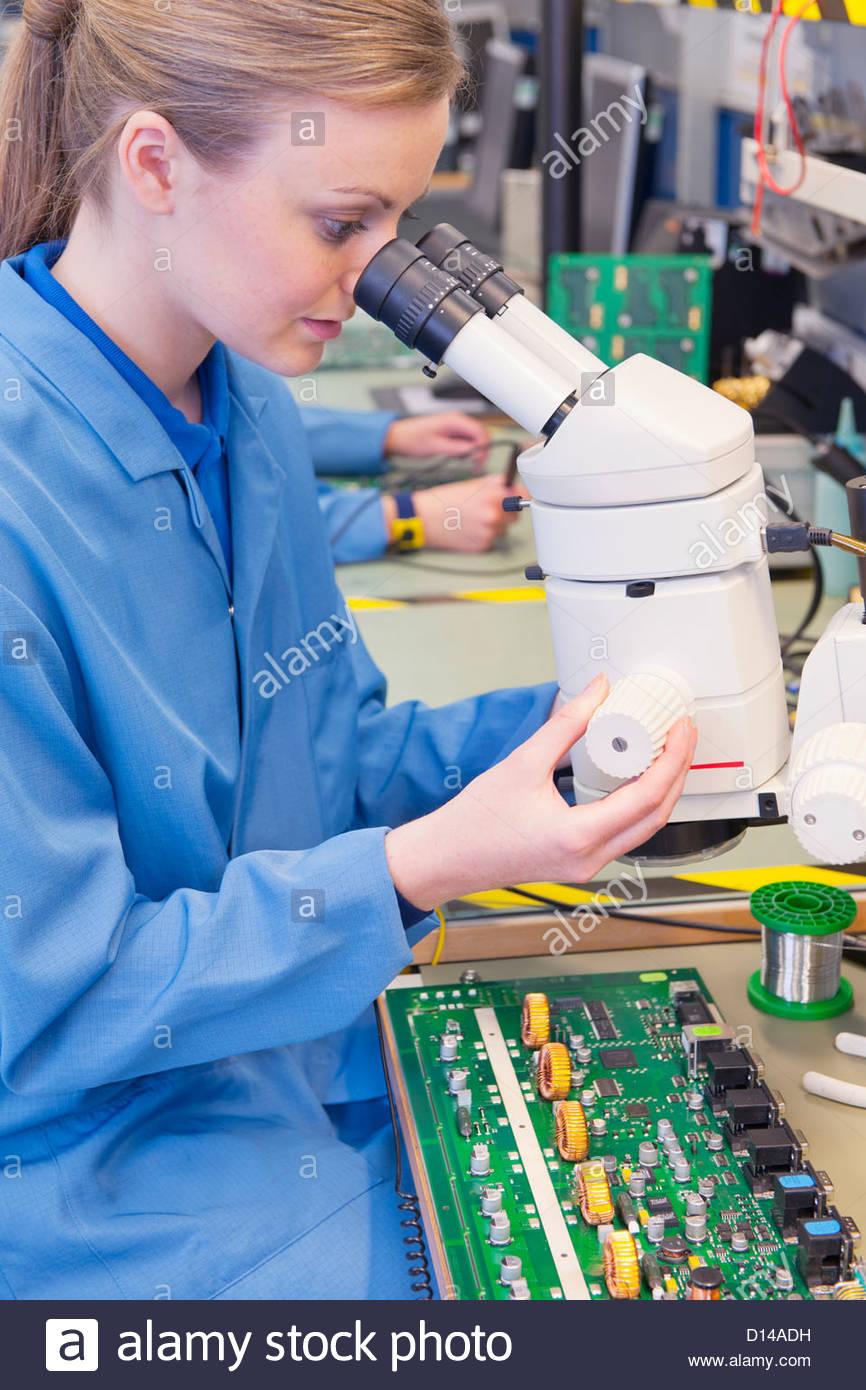 Techniker mit Mikroskop, Platine im Werk zu prüfen Stockbild