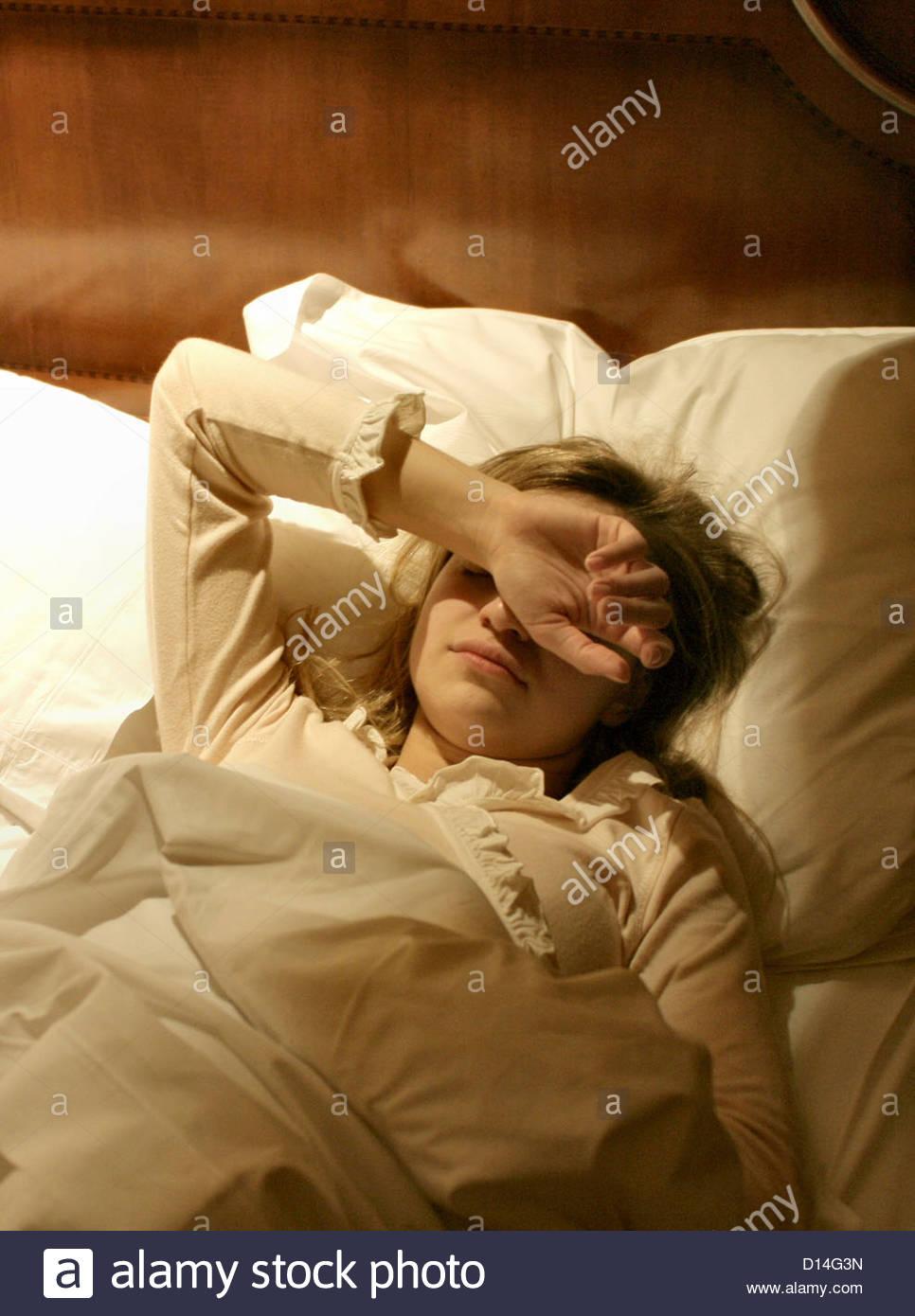 Frau im Bett zu erwachen Stockbild