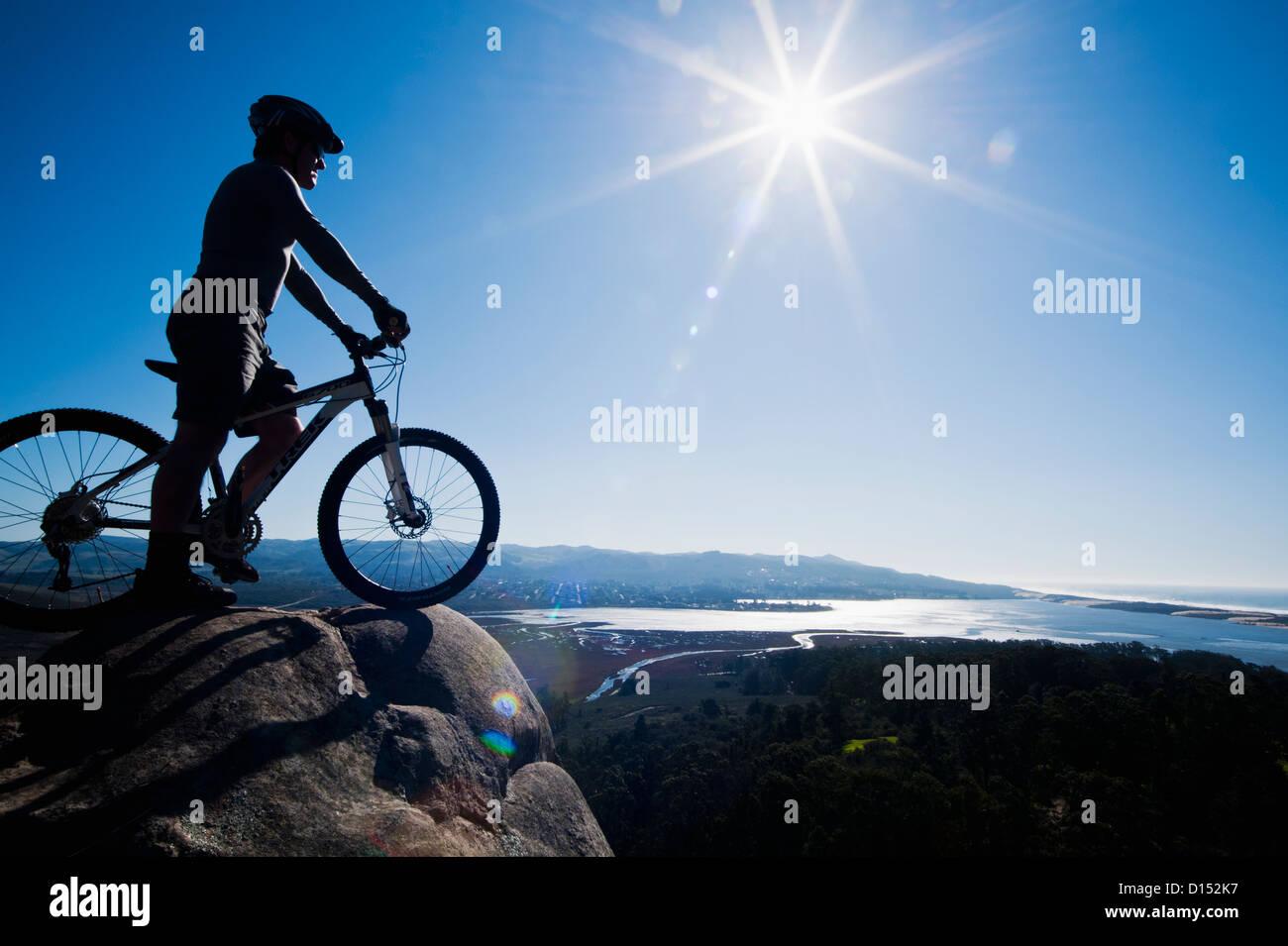 Kalifornien, Morro Bay State Park, Mann auf Fahrrad sieht über Morro Bay von Klippe. Stockbild