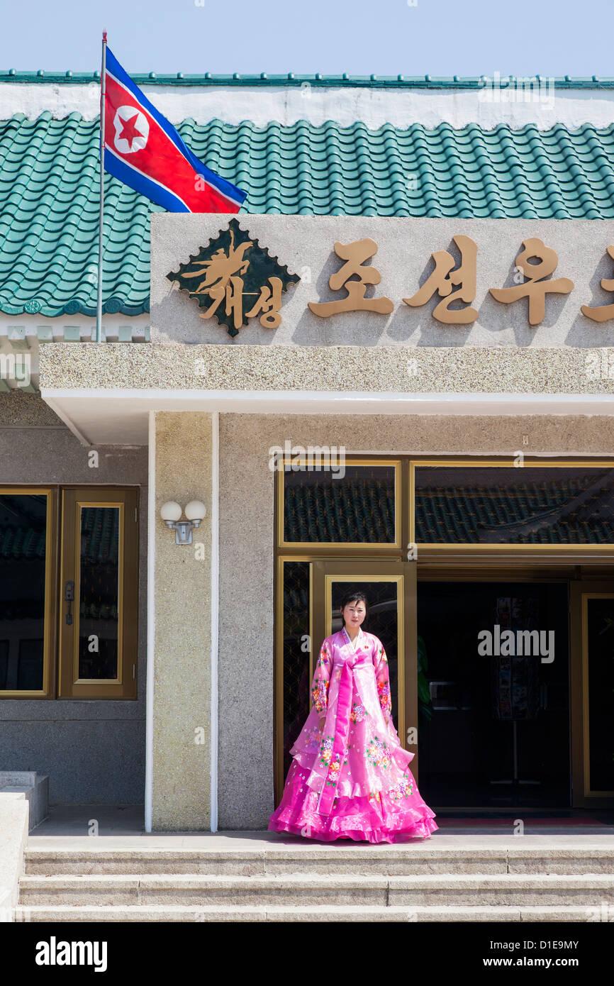 Frau in bunten Trachten am Eingang zum Tourist Shop, Demokratische Volksrepublik Korea (DVRK), Nordkorea Stockbild
