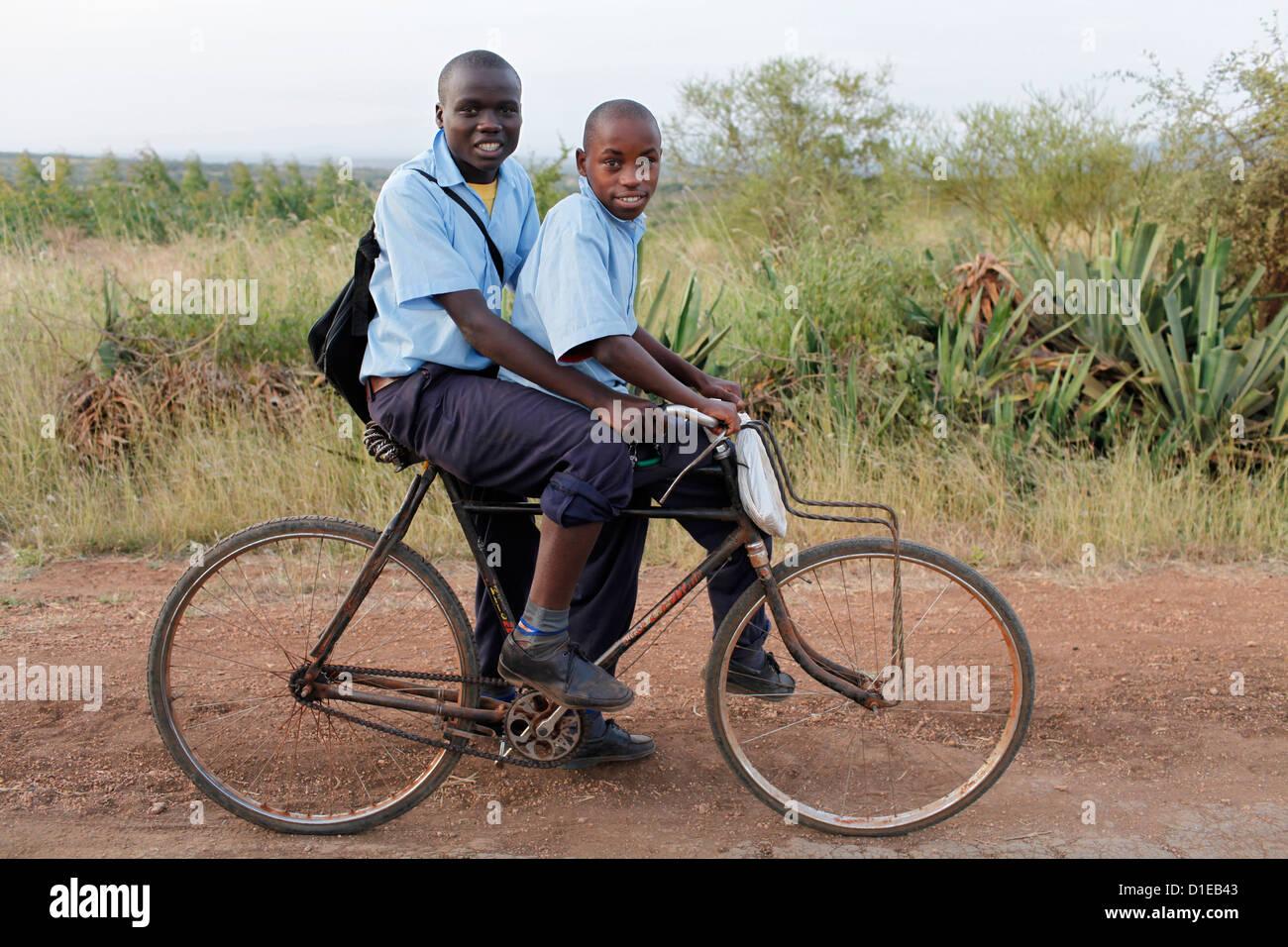 Schülerinnen und Schüler auf einem Fahrrad, Embu, Kenia, Ostafrika, Afrika Stockbild