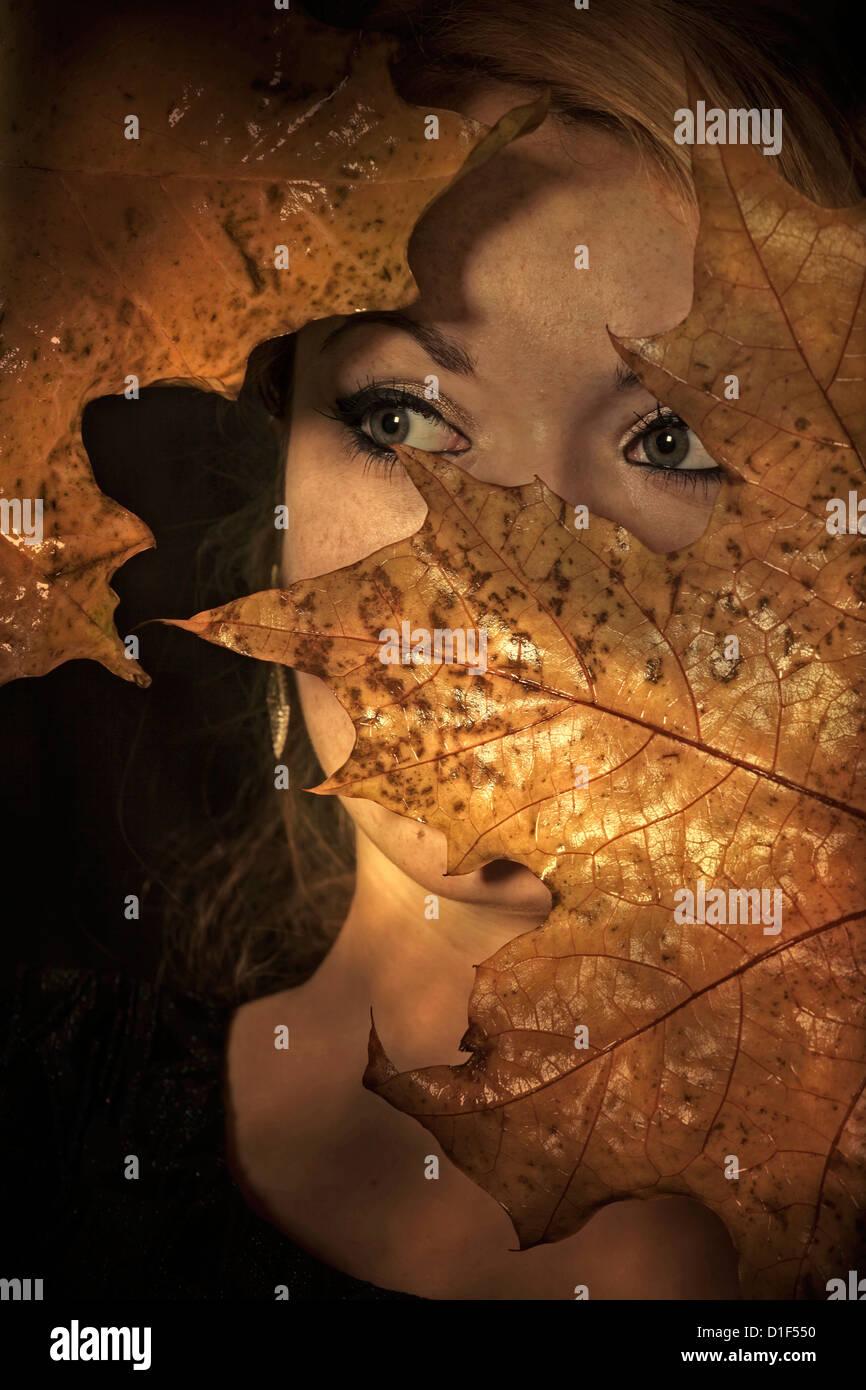 eine Frau sucht durch Blätter Stockbild