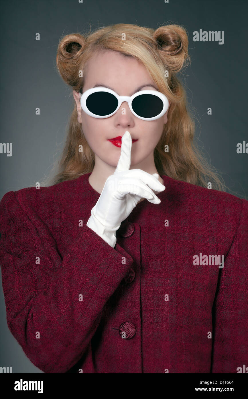 eine Frau in einem Vintage Blazer mit Vintage Sonnenbrillen im 50er Jahre Stil mit dem Finger auf den Lippen Stockbild