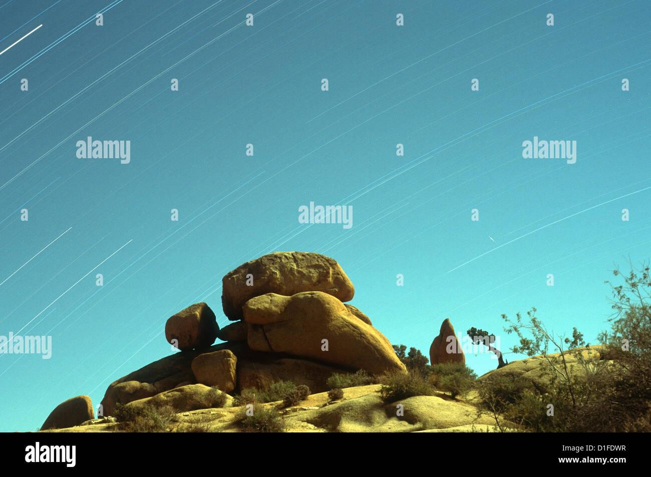 Zeitaufwand von Sternen mit Felsformationen in den Vordergrund, Joshua Tree Nationalpark, Kalifornien, USA Stockbild