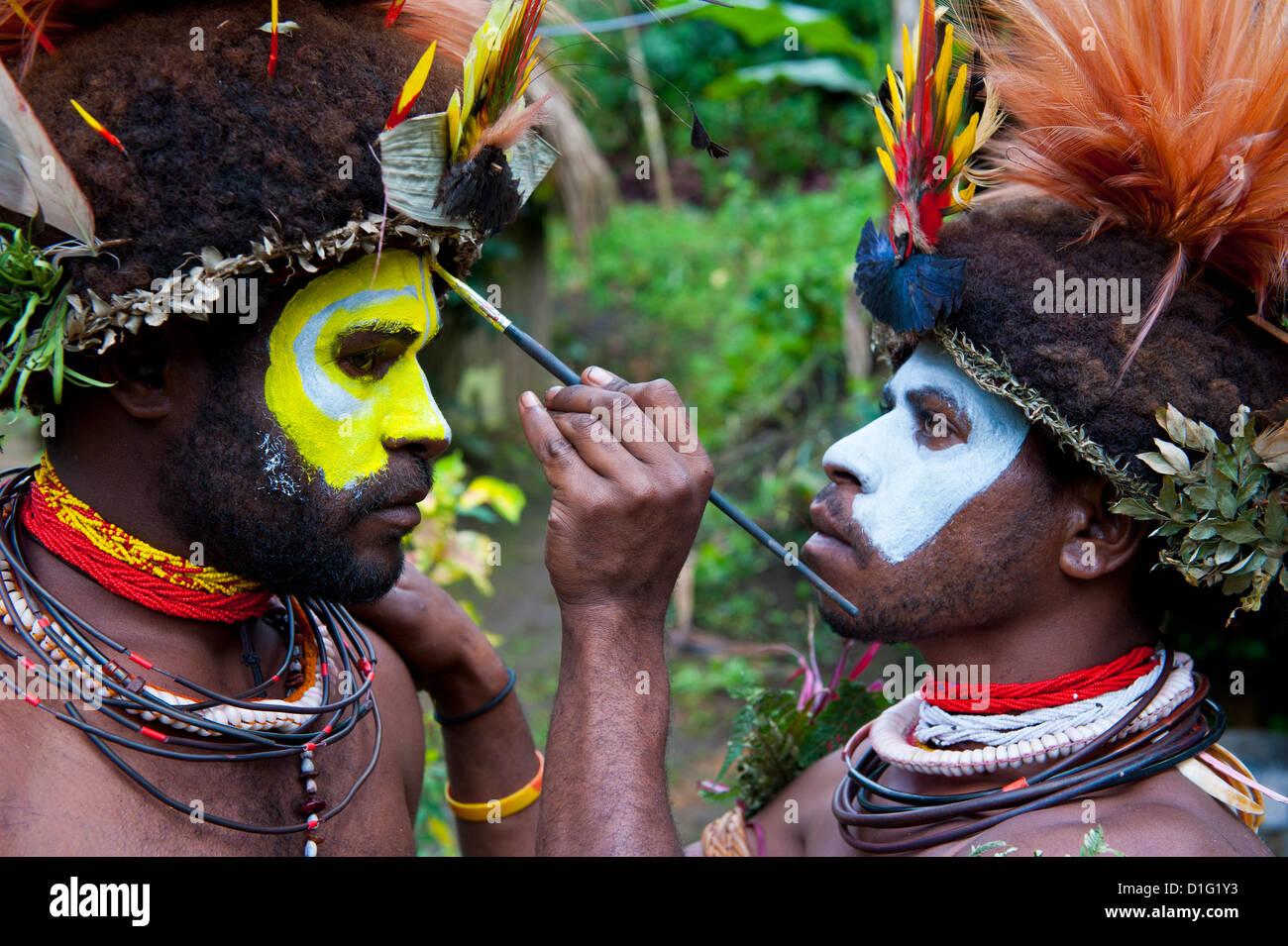 Stammesangehörigen setzen Farbe auf ihren Gesichtern zu feiern der traditionellen Sing Sing in Paya in den Stockbild