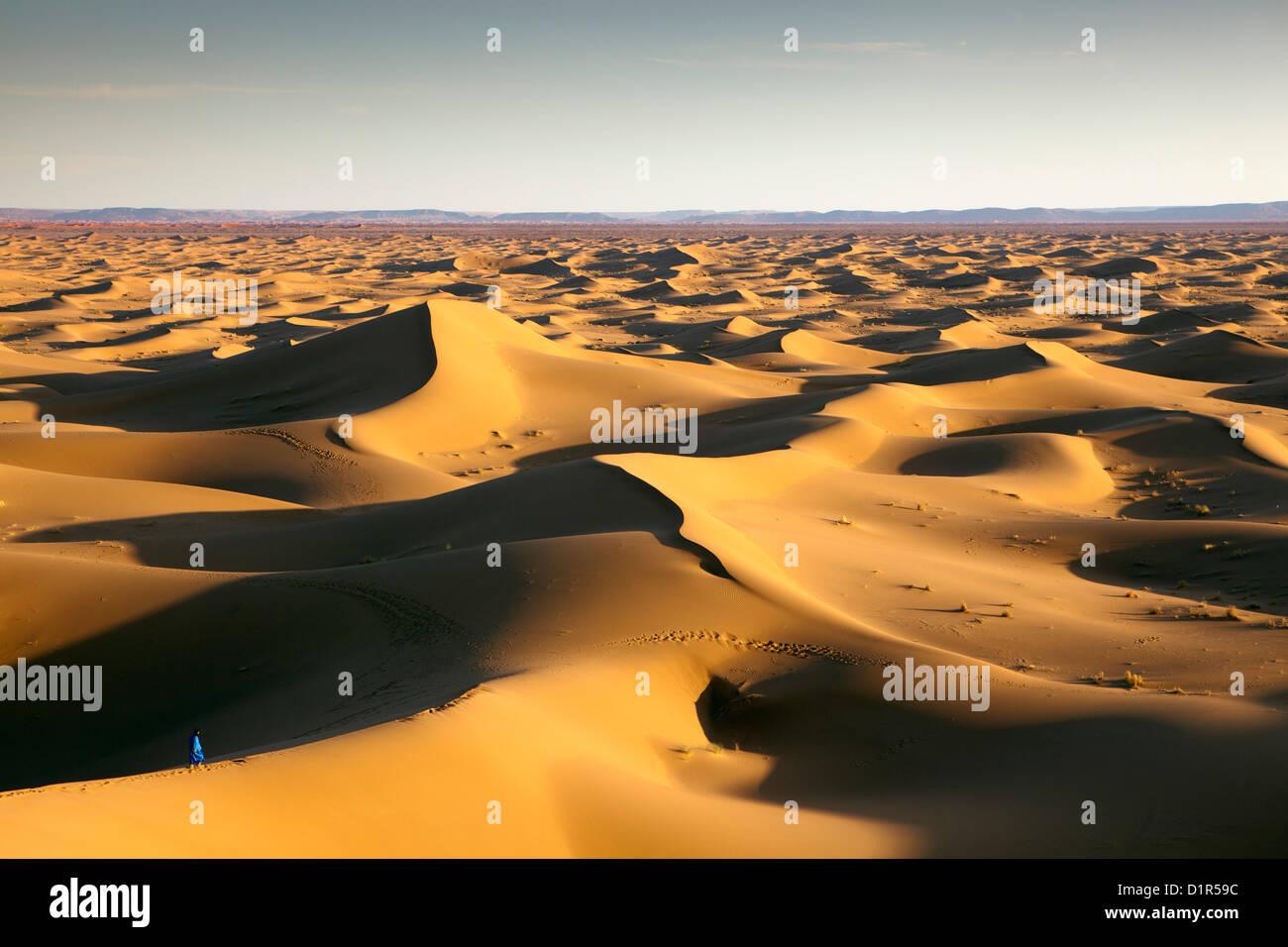 Marokko, M' Hamid, Erg Chigaga Dünen. Wüste Sahara. Lokalen Berber Mann auf Sanddüne, Hintergrund Stockbild