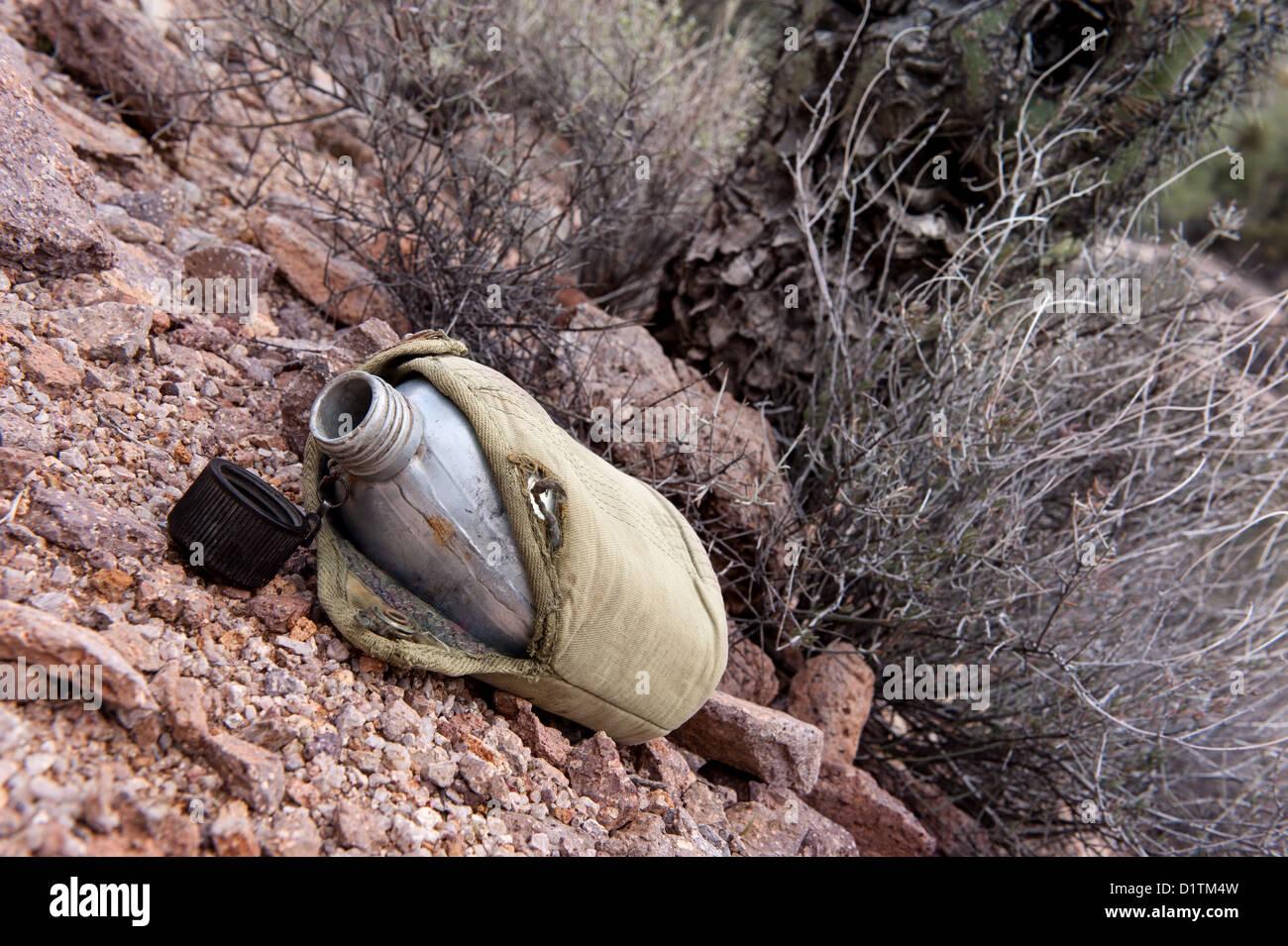 In einer trockenen, abgelegenen Wildnis der Wüste sitzt eine leere militärische Kantine vor trockenen Stockbild