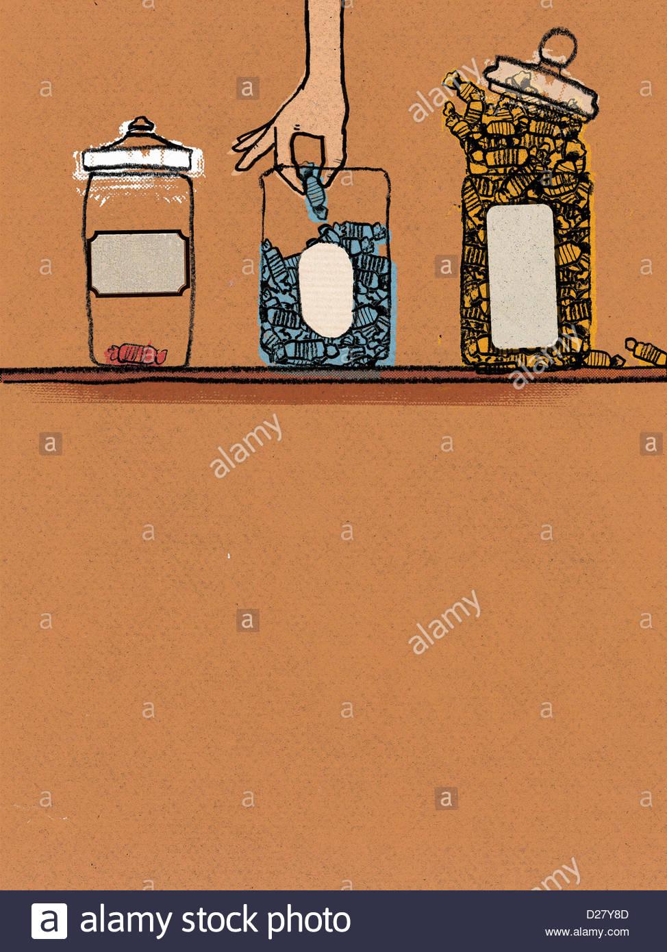 Hand Griff nach Süßigkeiten in Glas Stockfoto