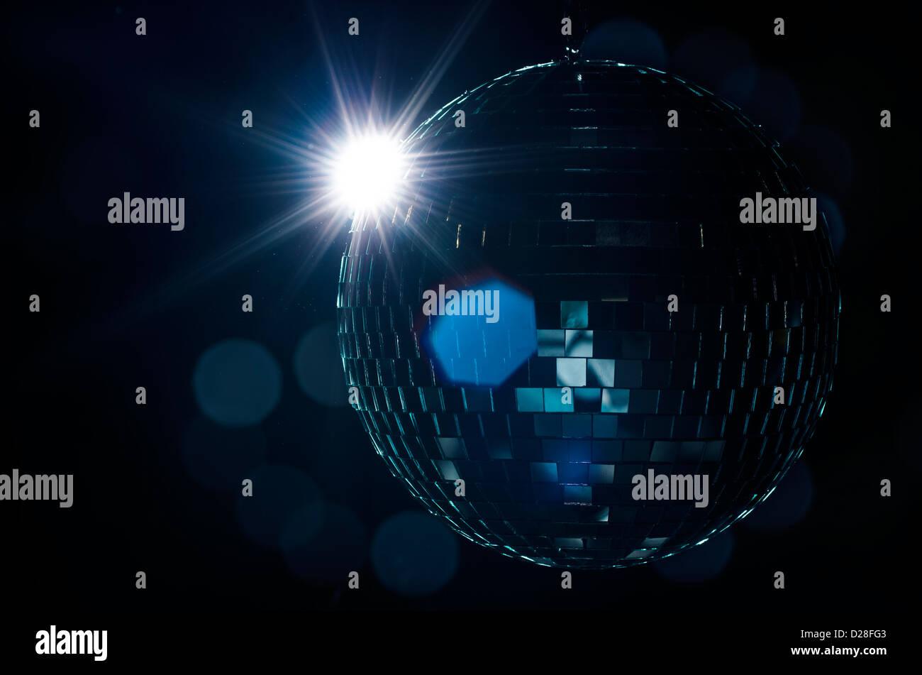 Eine Disco-Kugel mit leichten Flair und verschwommenen Lichtern auf Hintergrund. Ein Nachtleben Bild als Beispiel Stockbild
