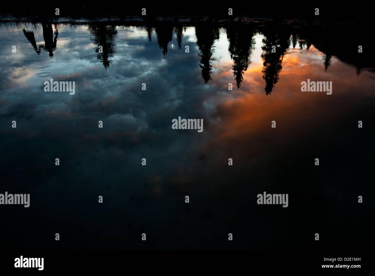 Ein Mann kopfüber in einen See mit bunten Wolken und Regentropfen reflektiert. Stockbild
