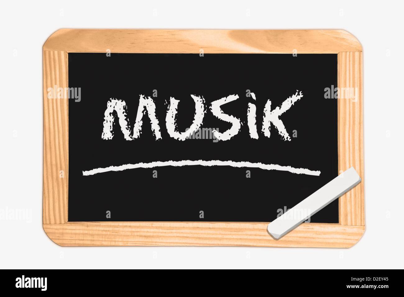 Detail-Foto von einer Tafel mit der deutschen Aufschrift Musik, weiße Kreide liegt in einer Ecke Stockbild
