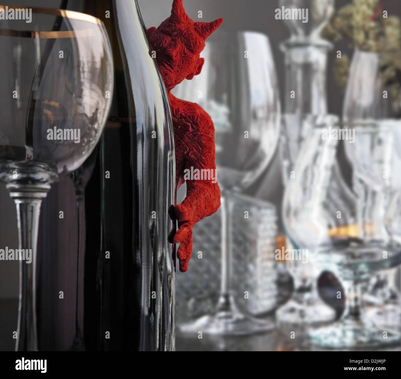 ein kleiner Roter Teufel späht heraus von hinten eine Flasche Wein. Einige Gläser sind auf den eingelegten Stockbild
