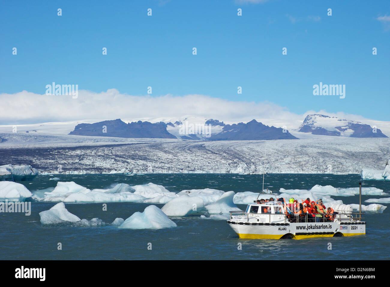 Amphibienfahrzeug zwischen Eisbergen am Gletschersee am Jökulsárlón mit Eiskappe des Vatnajökull Stockbild
