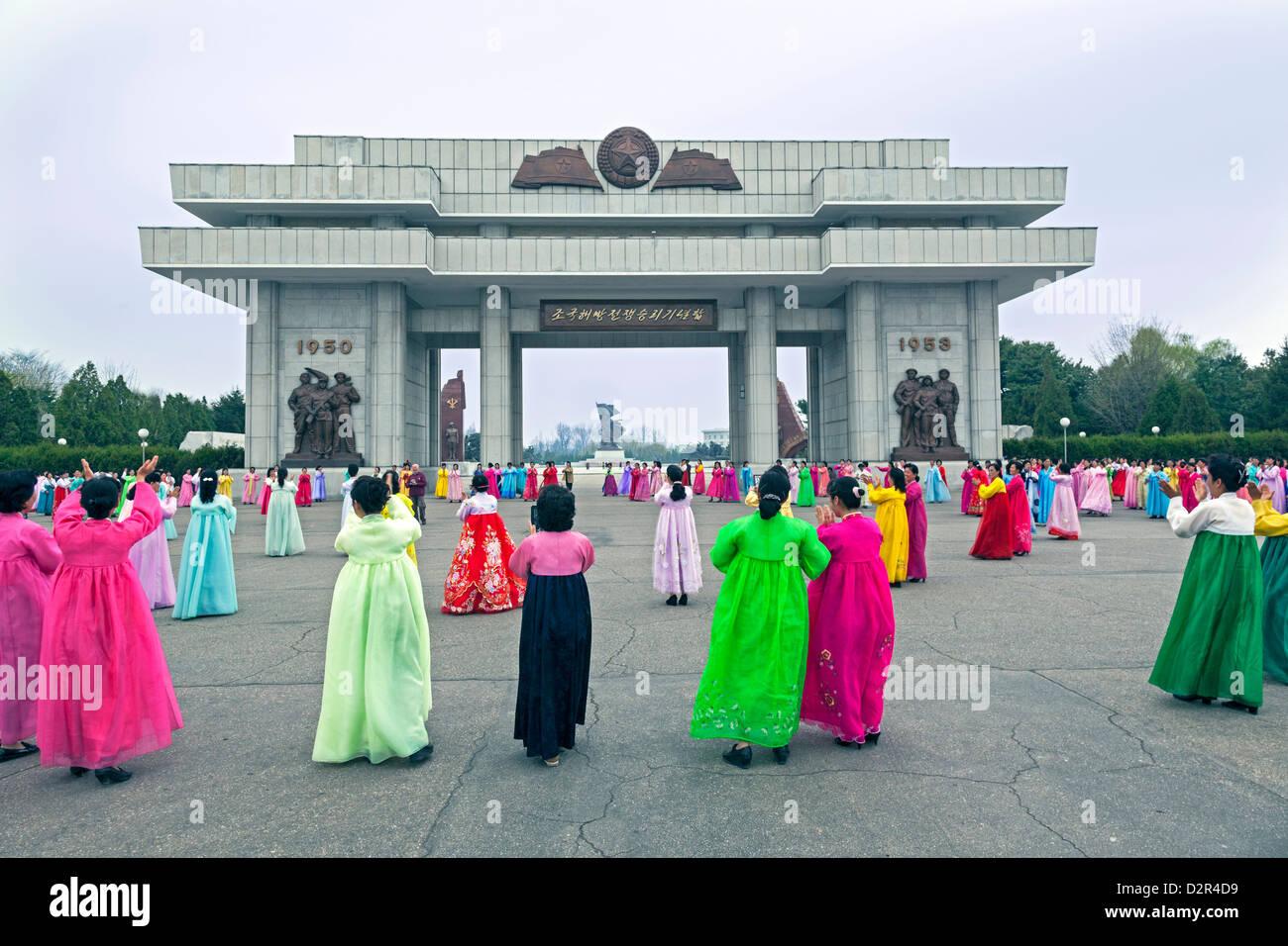 Frauen in bunten traditionellen Kleidern an Masse tanzen, Pyongyang, Nordkorea Stockbild