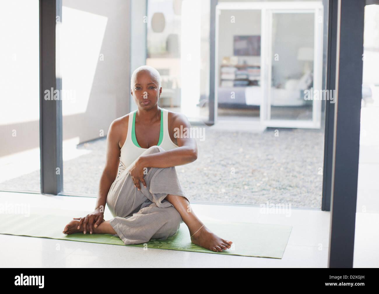 Ältere Frau erstreckt sich auf Yoga-Matte Stockbild