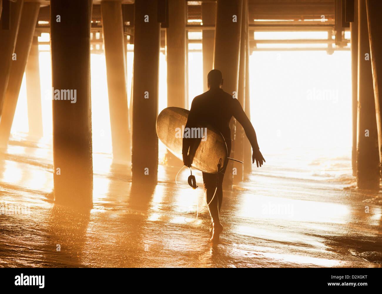 Ältere Surfer tragen Board unter pier Stockbild
