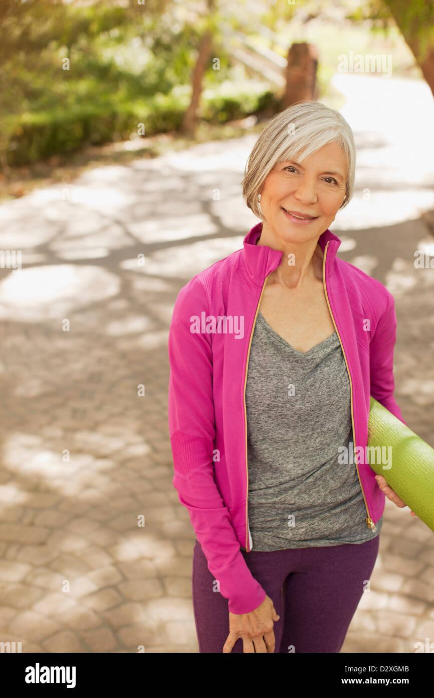 Ältere Frau, die Yoga-Matte im freien Stockbild