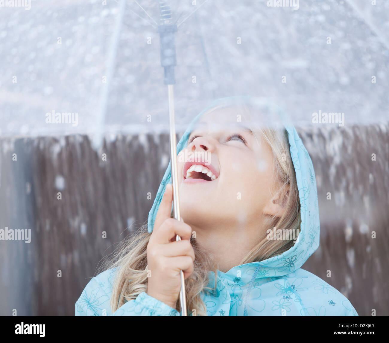 Nahaufnahme von Mädchen unter Dach blickte zu Platzregen Stockbild
