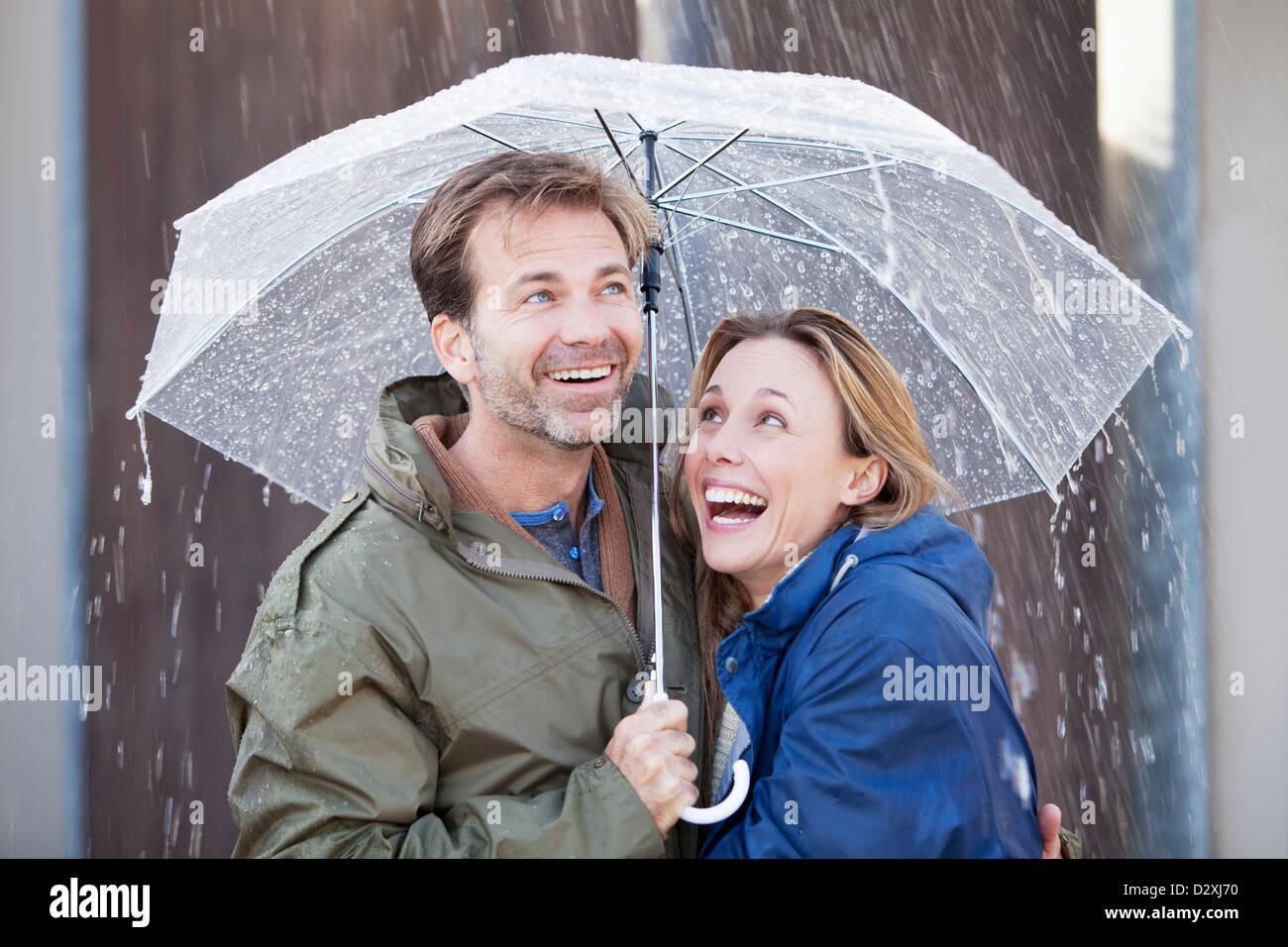 Glückliches Paar unter Dach im Regen Stockbild