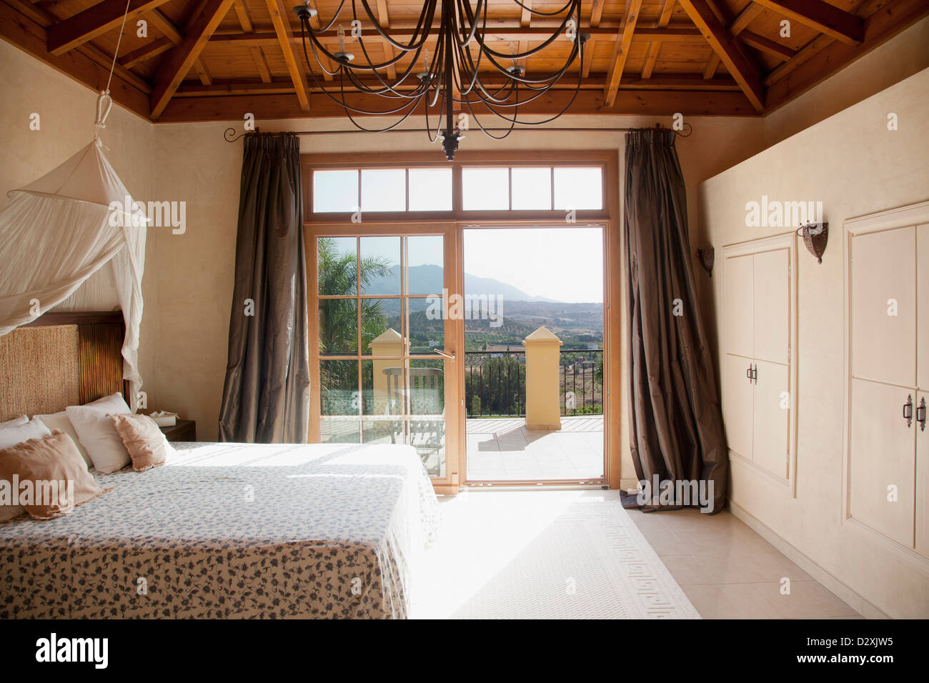 Bett mit Baldachin und Französisch Türen zum Balkon im Schlafzimmer ...