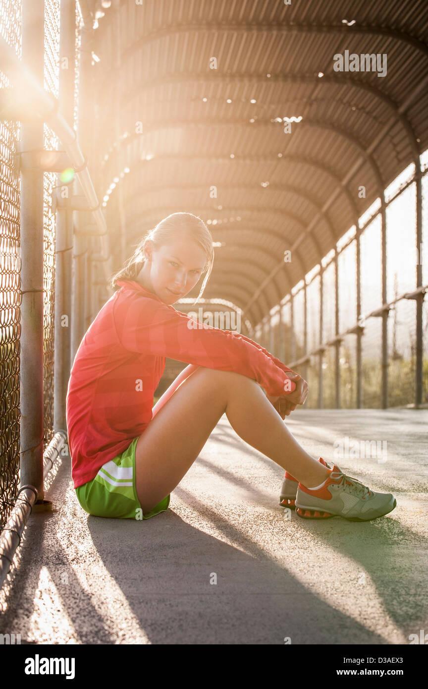 Frau sitzt auf städtischen Steg Stockbild