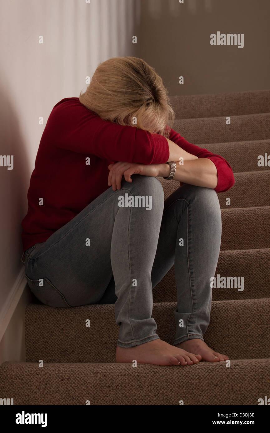 Blonde Frau sitzt alleine auf der Treppe, Leiter beugte sich nach vorn umkippen oder Weinen. Stockbild