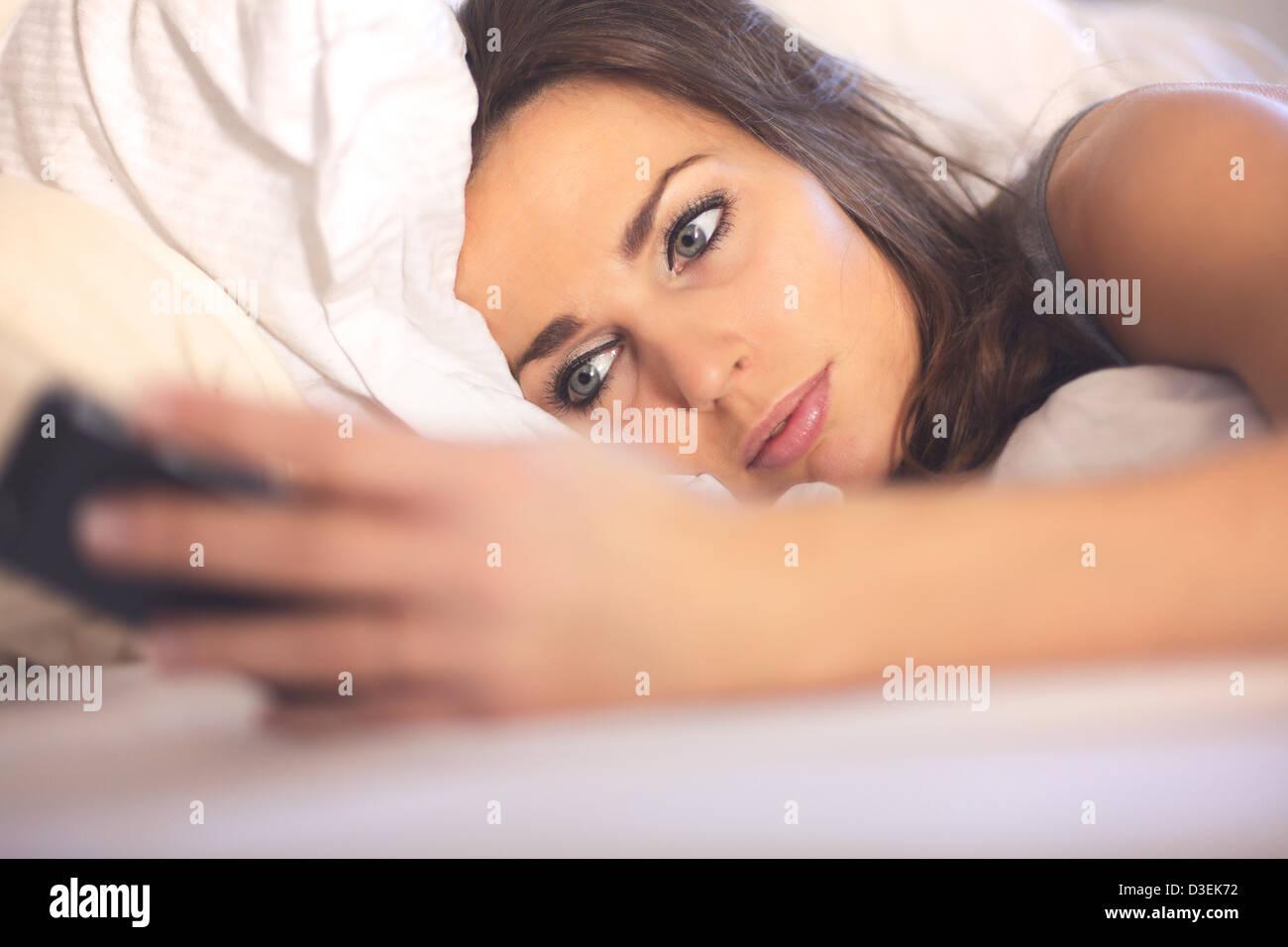 Frau liegt im Bett und Las SMS von ihrem smartphone Stockbild