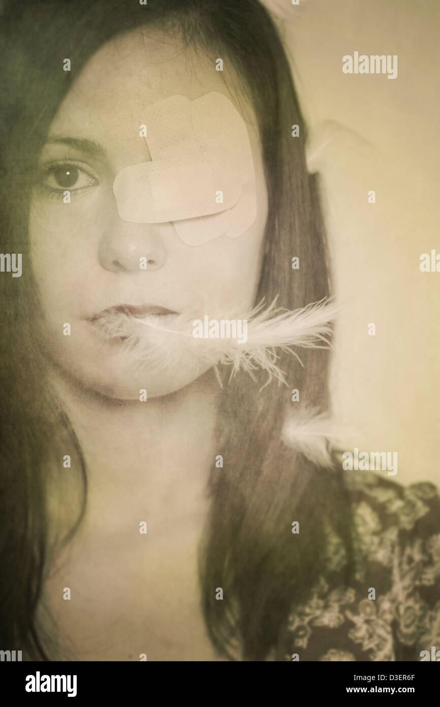 ein Mädchen mit Patches auf eines ihrer Augen und eine Feder im Mund Stockbild