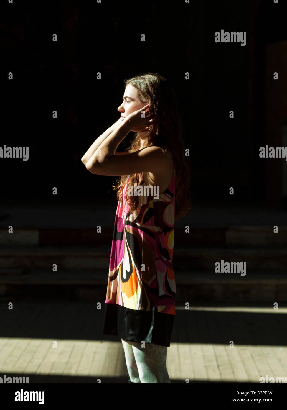 Frau, die im Sonnenlicht Stockbild