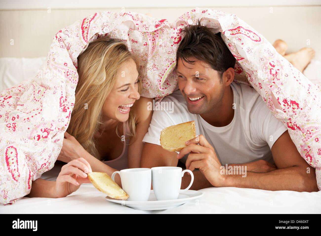 Paar kuschelte sich unter die Bettdecke zu frühstücken Stockbild