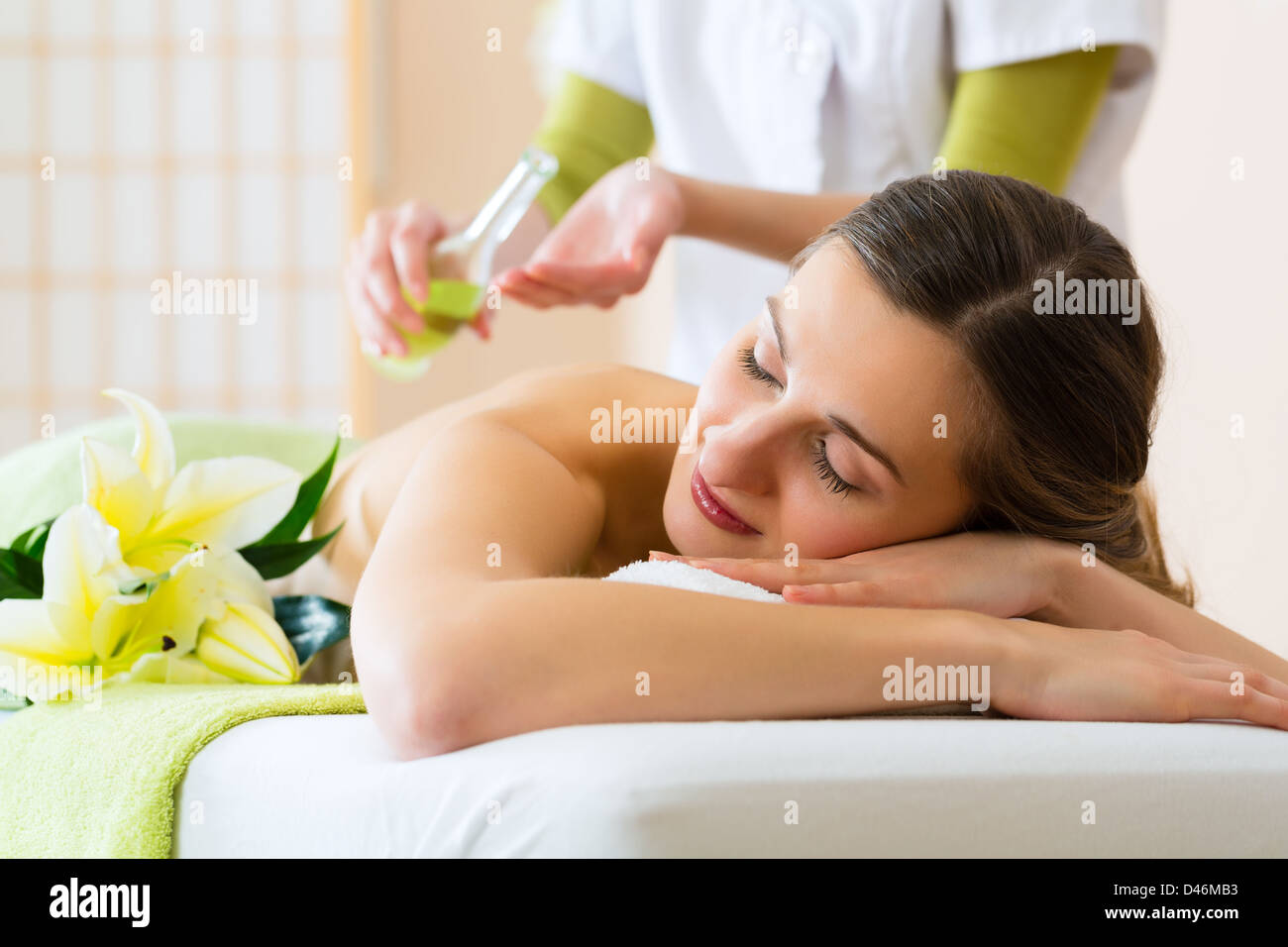 Schöne Frau, die einen Wellness Massage und sichtlich ein gutes Gefühl über es zurück Stockbild