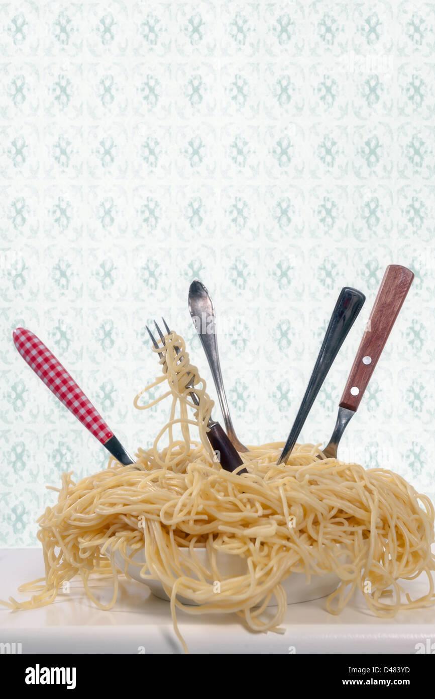 ein Teller voll Spaghetti mit fünf Gabeln Stockbild