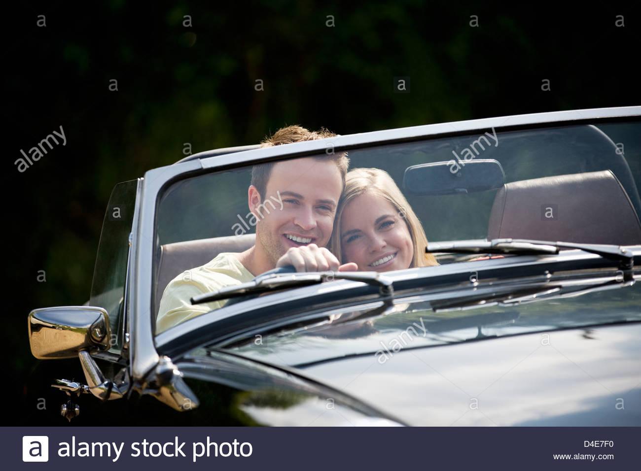 Ein junges Paar ein schwarzer Sportwagen Stockbild