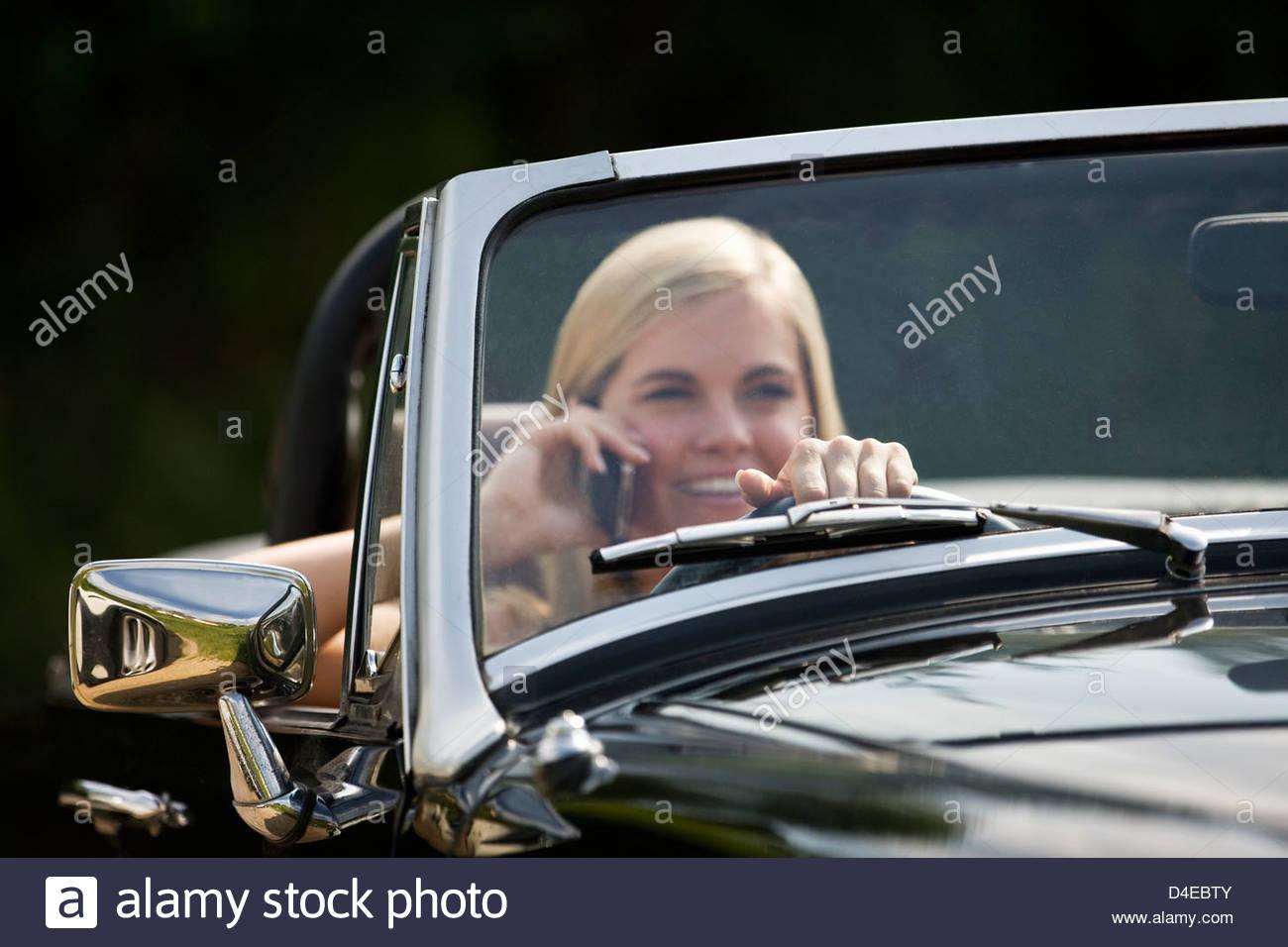 Eine junge Frau, die eine schwarze Sportwagen mit einem Mobiltelefon Stockbild
