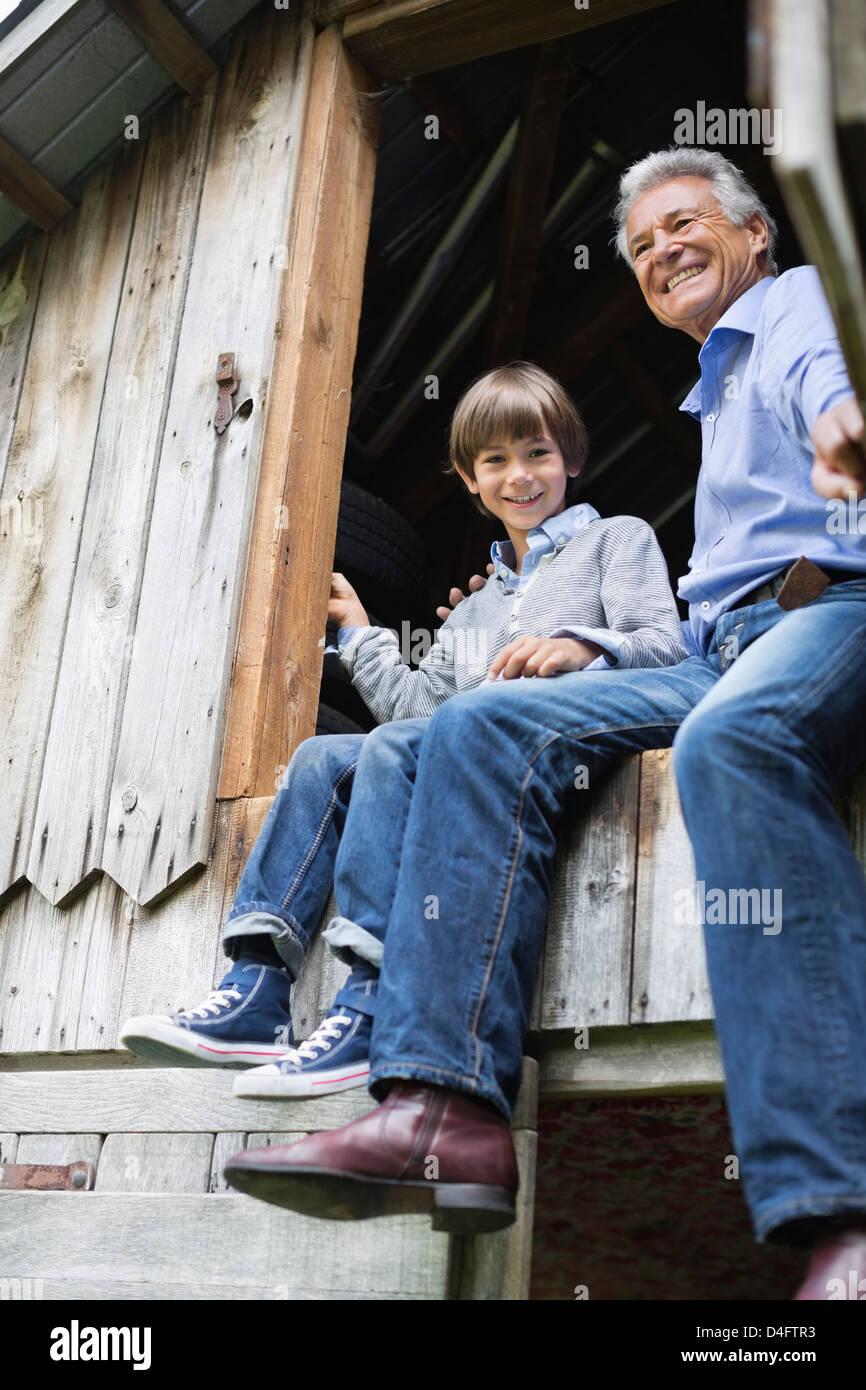 Mann und Enkel sitzen in Tür Stockbild