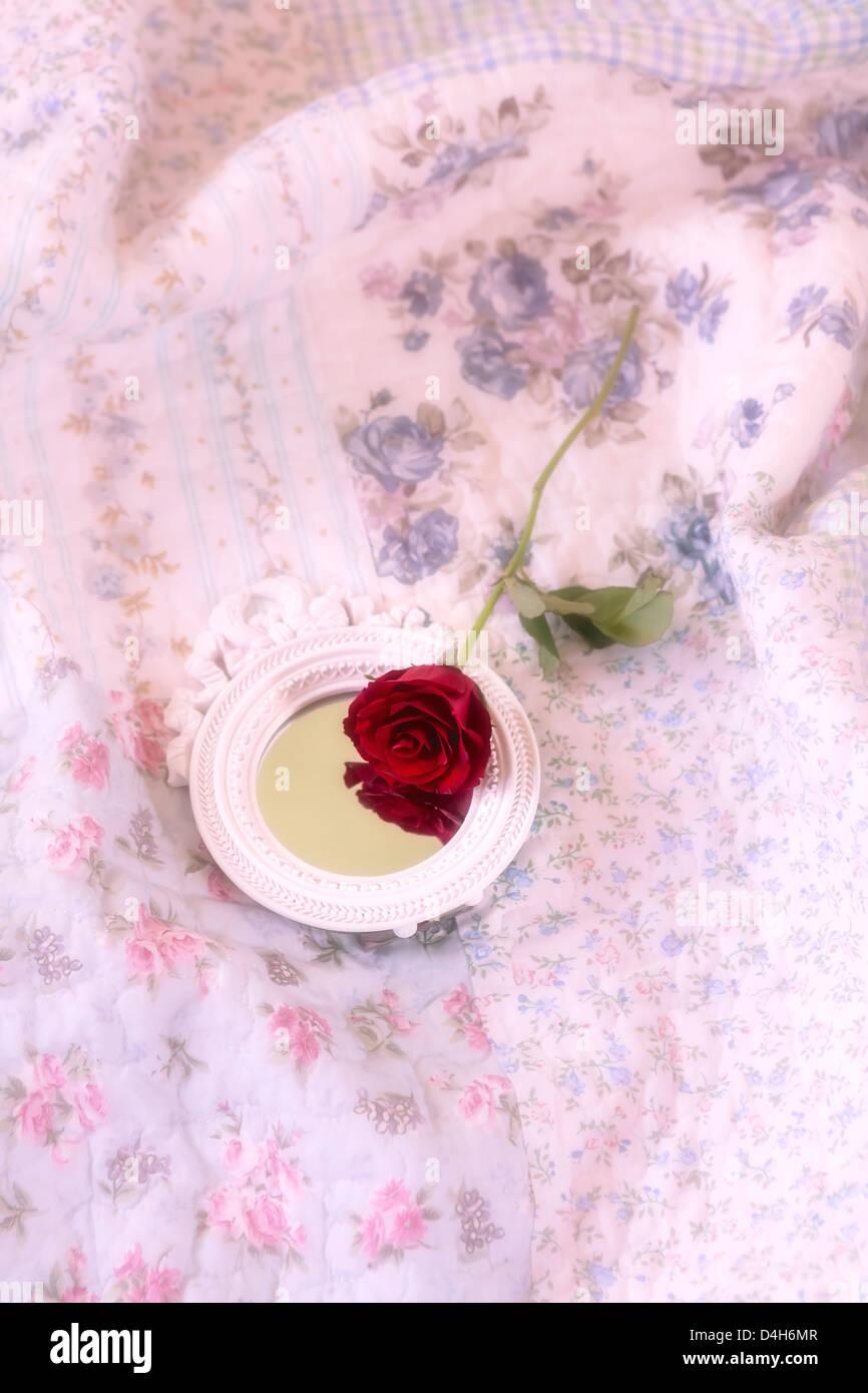 eine rote Rose und ein Spiegel auf einem Vintage Bett Stockbild