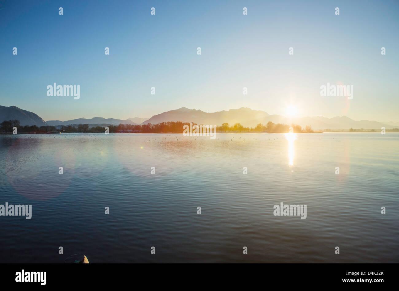 Sonne über noch ländliche See und Berge Stockbild