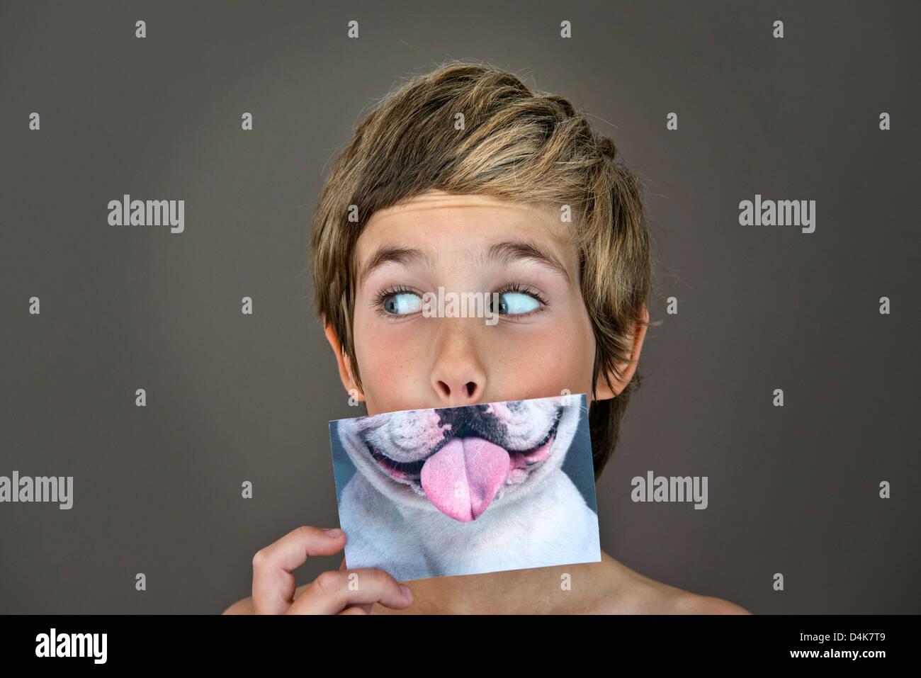 Junge mit Bild des Hundes über Gesicht Stockbild