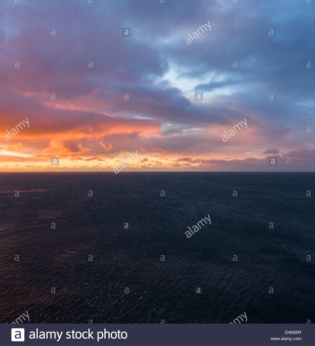 Sonnenaufgang über dem Meer bei bewölktem Himmel Stockbild