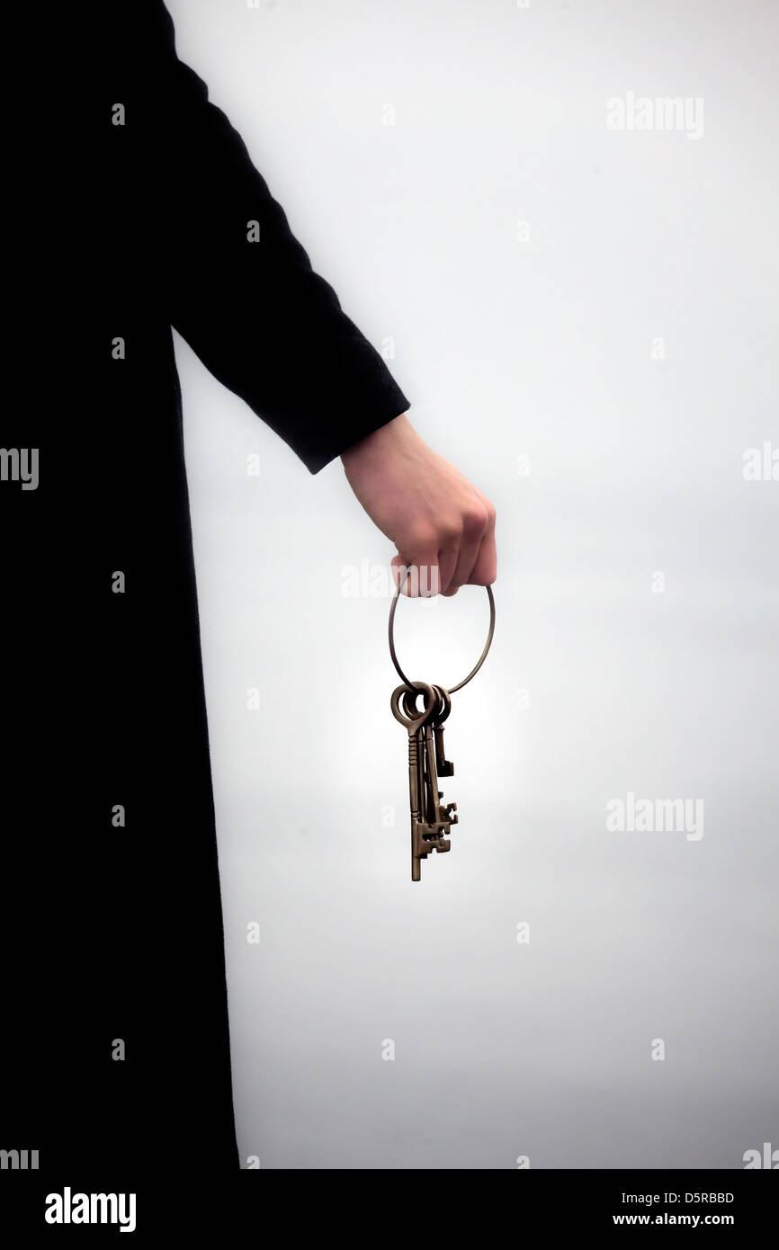 ein Mann in einem schwarzen Mantel hält einen Schlüsselring mit alten Schlüsseln Stockbild